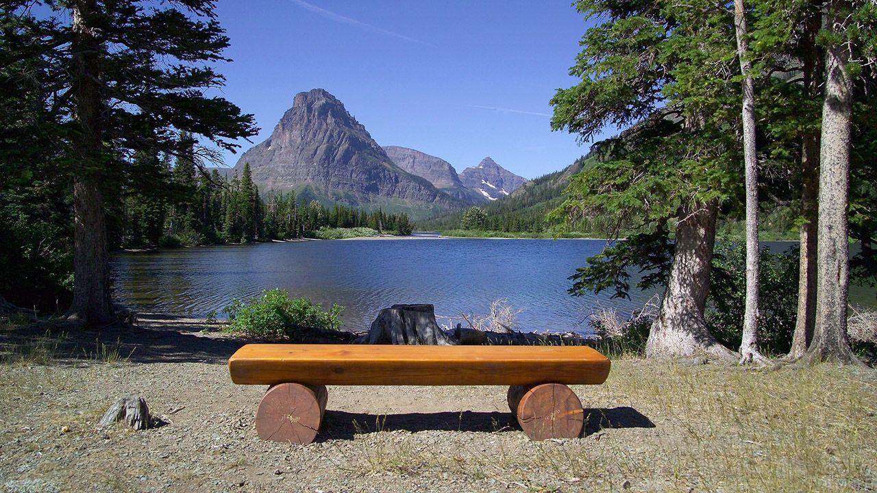 Лавка из брёвен у озера на фоне гор