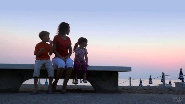 Мама с детьми на скамейке у моря