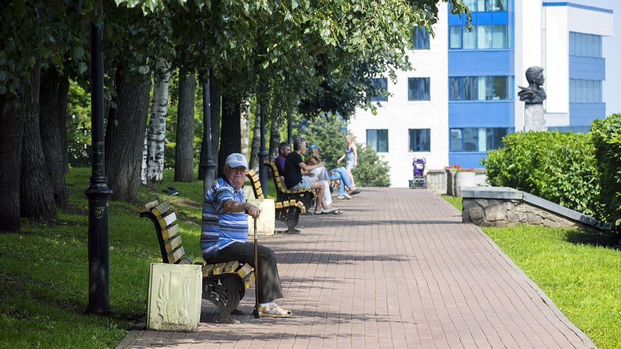 Пенсионер на скамейке городского парка