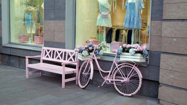 Розовая скамейка и декоративный велосипед-клумба у витрины магазина