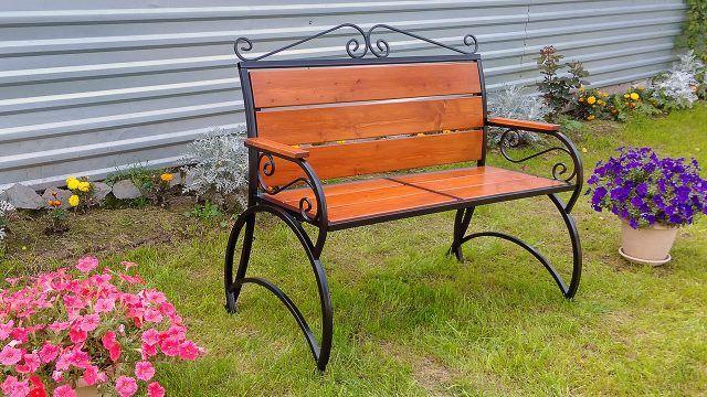 Садовая скамейка на лужайке с цветами