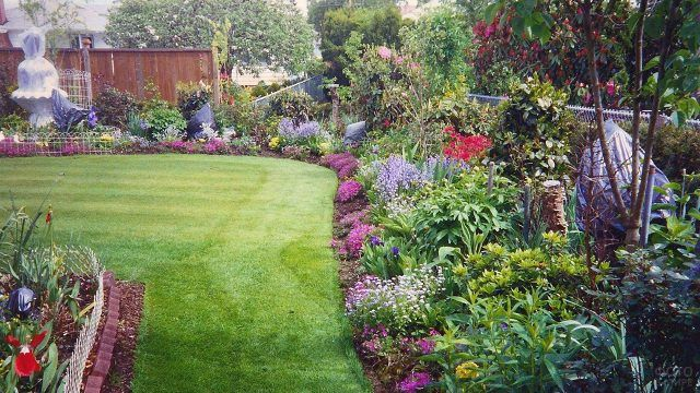Цветочное оформление лужайки на заднем дворе частного дома