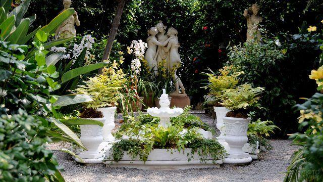 Декоративная белая клумба из гипса в зелёном саду с античными скульптурами