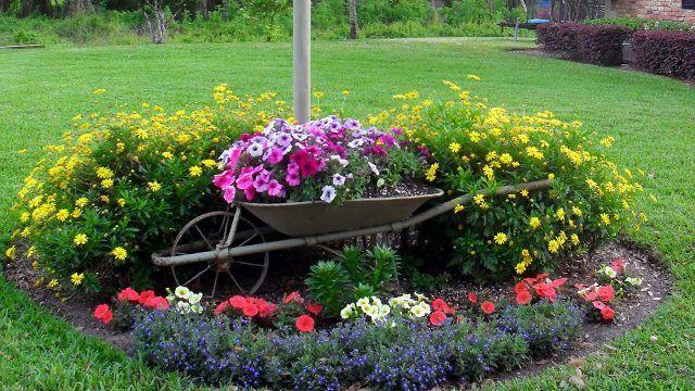Декоративная круглая цветочная клумба с садовой тачкой