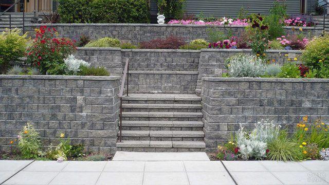 Многоуровневая каменная клумба у лестницы с цветочным ассорти в английском стиле