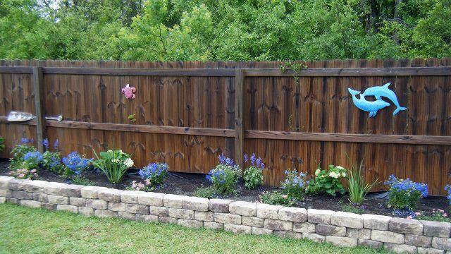 Начало цветения голубой клумбы с каменным бордюром вдоль деревянного забора
