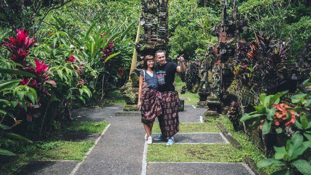 Пара туристов среди цветущих тропических клумб