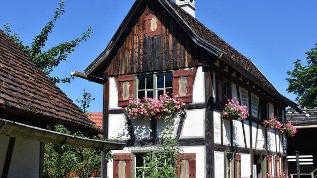Подвесные клумбы с розовыми цветами под окнами европейского сельского домика
