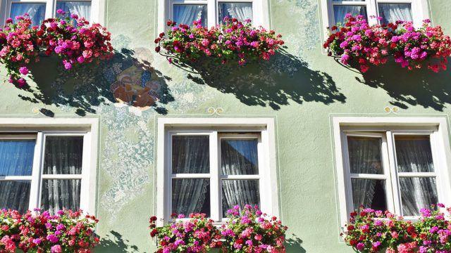 Висячие клумбы с ярко-розовыми цветами на фасаде дома