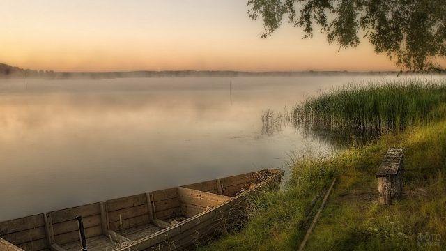 Деревянная лодка и лавочка на берегу реки