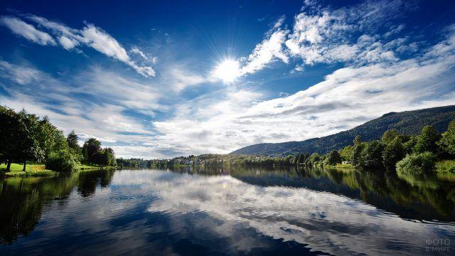 Облака и солнце отражаются в реке
