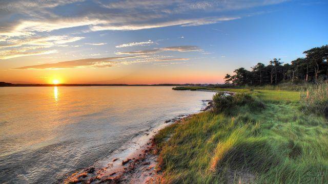 Травянистый берег реки и закат