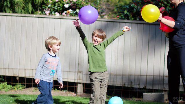 Довольные малыши играют во дворе с воздушными шариками
