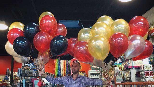 Курьер с двумя букетами воздушных шариков с гелием