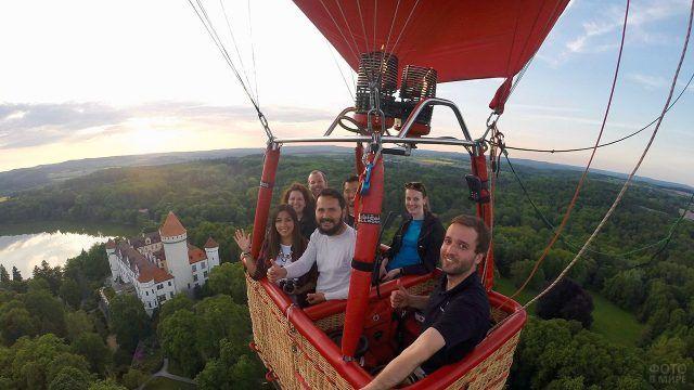 Люди фотографируются в корзине воздушного шара над уровнем горизонта