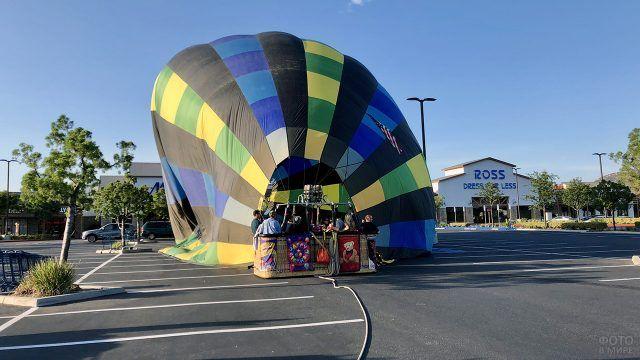 Люди надувают воздушный шар горячим воздухом
