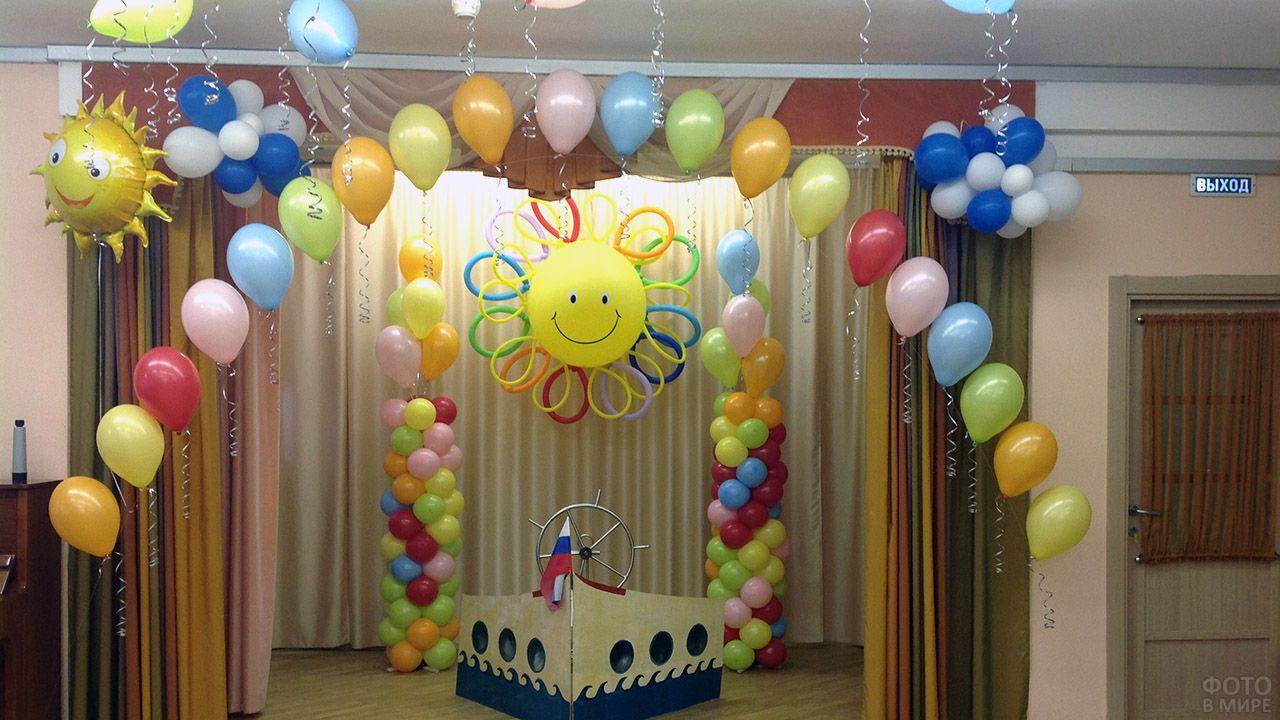 Оформление сцены разноцветными шариками в виде радуги над солнечным небом