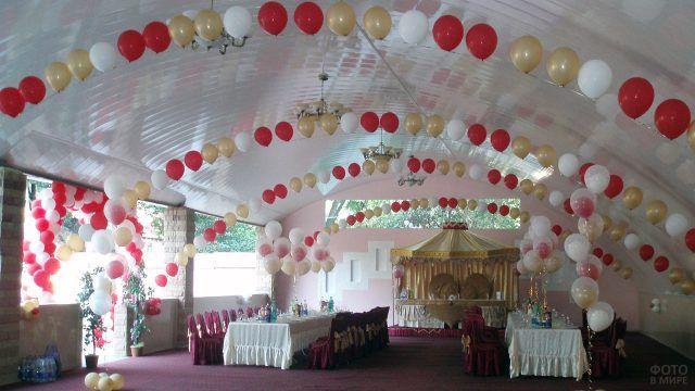 Оформление сводчатого потолка воздушными шариками в бело-золотой гамме с красными акцентами