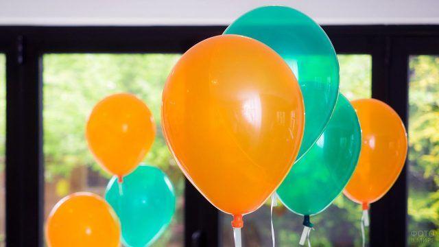 Оранжевые и зелёные воздушные шарики на фоне окна
