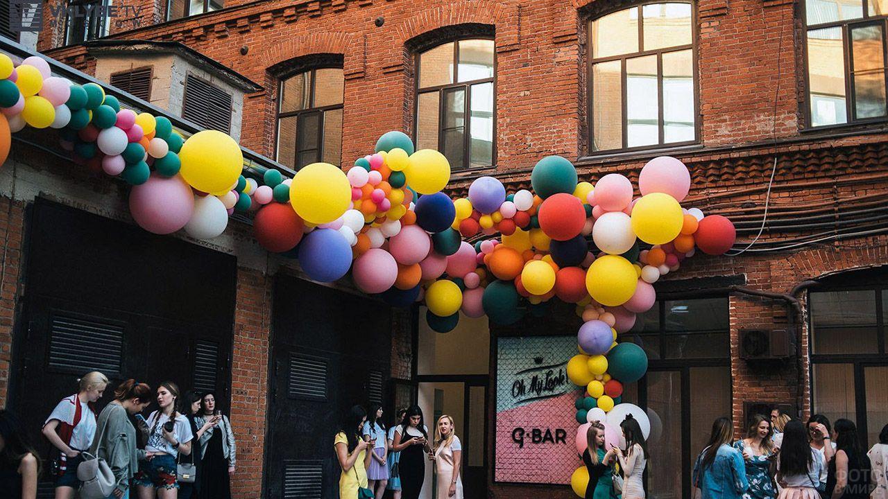 Пёстрая гирлянда из воздушных шариков разных размеров на кирпичном фасаде