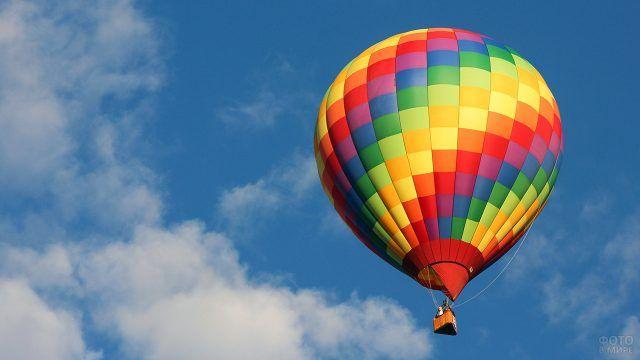 Радужный воздушный шар летит в небе