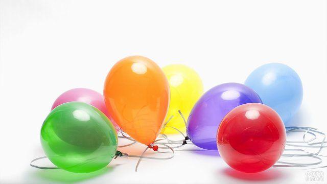 Разноцветные воздушные шарики лежат на белом фоне