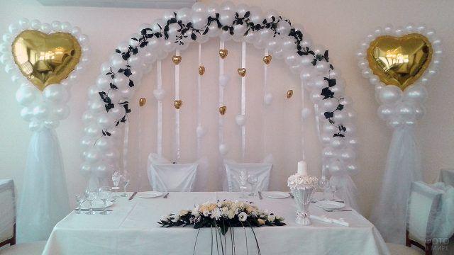 Свадебная арка и колонны из белых шариков с золотыми колоннами
