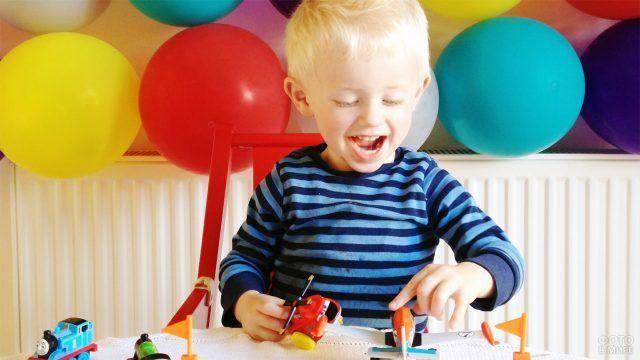 Светловолосый мальчик играет на фоне стены с разноцветными шариками