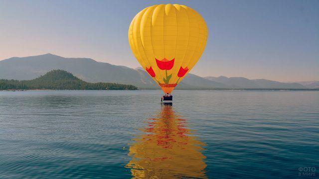 Жёлтый воздушный шар на поверхности воды