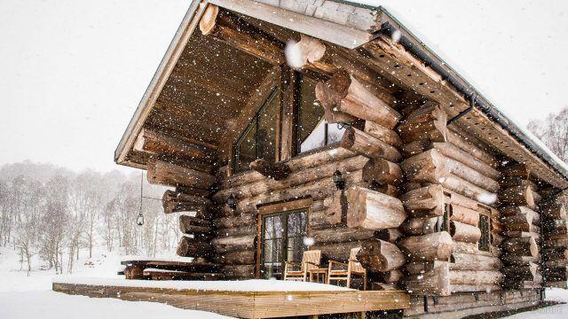 Аутентиный бревенчатый эко-дом под снегопадом