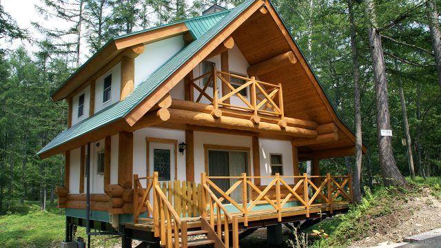 Белый бревенчатый домик с высоким крыльцом и балконом на втором этаже