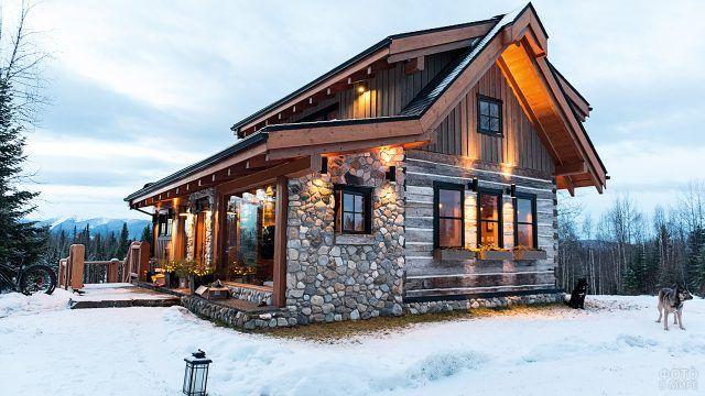 Бревенчатое шале с каменной отделкой фасада в зимних горах