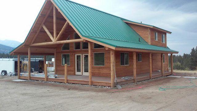 Бревенчатый дом в канадском стиле с зелёной крышей