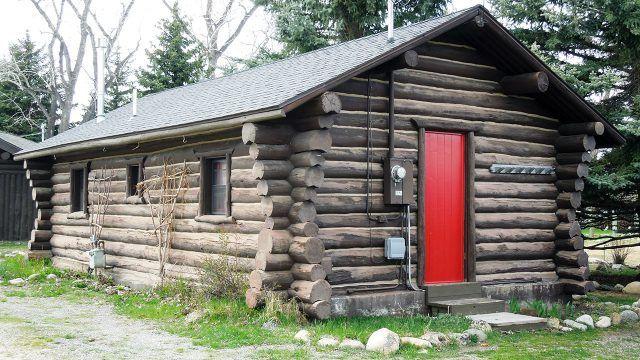 Бревенчатый лесной домик с красной дверью