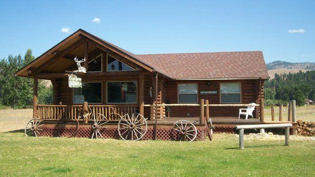 Декорированное в аутентичном стиле крыльцо бревенчатого загородного дома