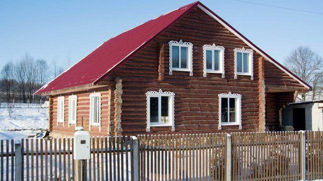 Деревенский сруб из кругляка с красной крышей и белыми наличниками