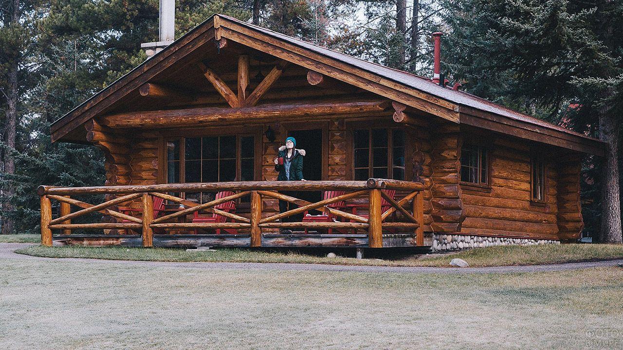 Девушка стоит на веранде с красными креслами бревенчатого канадского дома