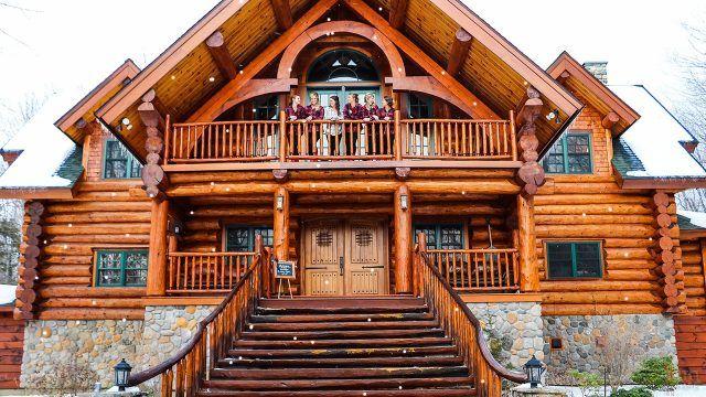 Девушки в зимний день на балконе мансардного этажа деревянного сруба из кругляка