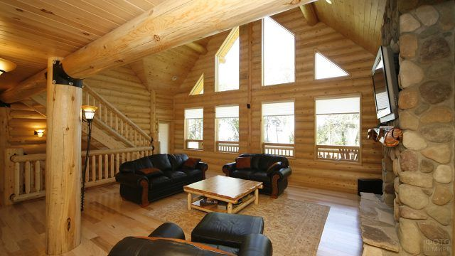 Гостиная с камином и кожаными диванами в бревенчатом эко-доме