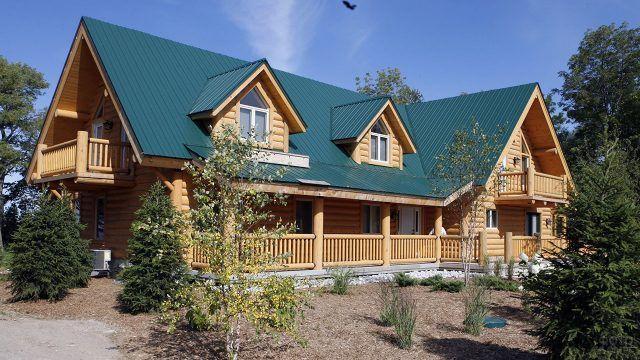 Просторный двухэтажный бревенчатый дом с верандой и балконами под зелёной крышей