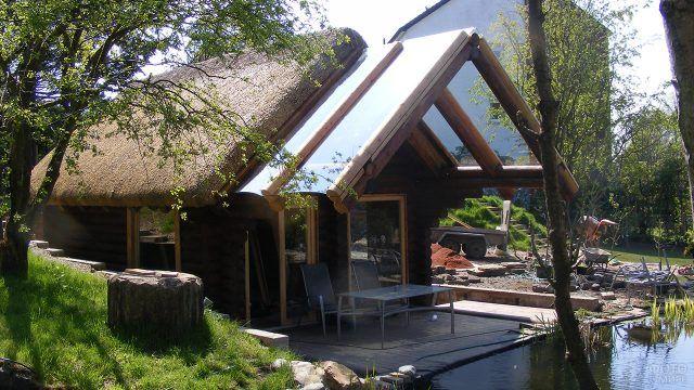 Современный бревенчатый эко-дом с соломенной крышей на берегу тенистого пруда