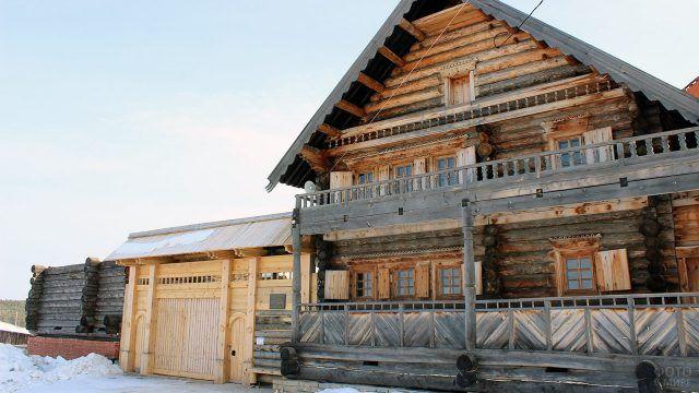 Старинный двухэтажный бревенчатый дом с новыми воротами