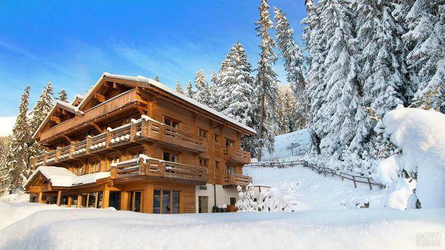 Заснеженный бревенчатый сруб горнолыжного отеля