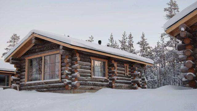 Заснеженный финский бревенчатый домик в сугробе