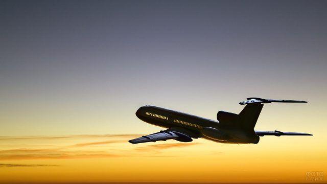 Абрис пассажирского самолёта на фоне заката