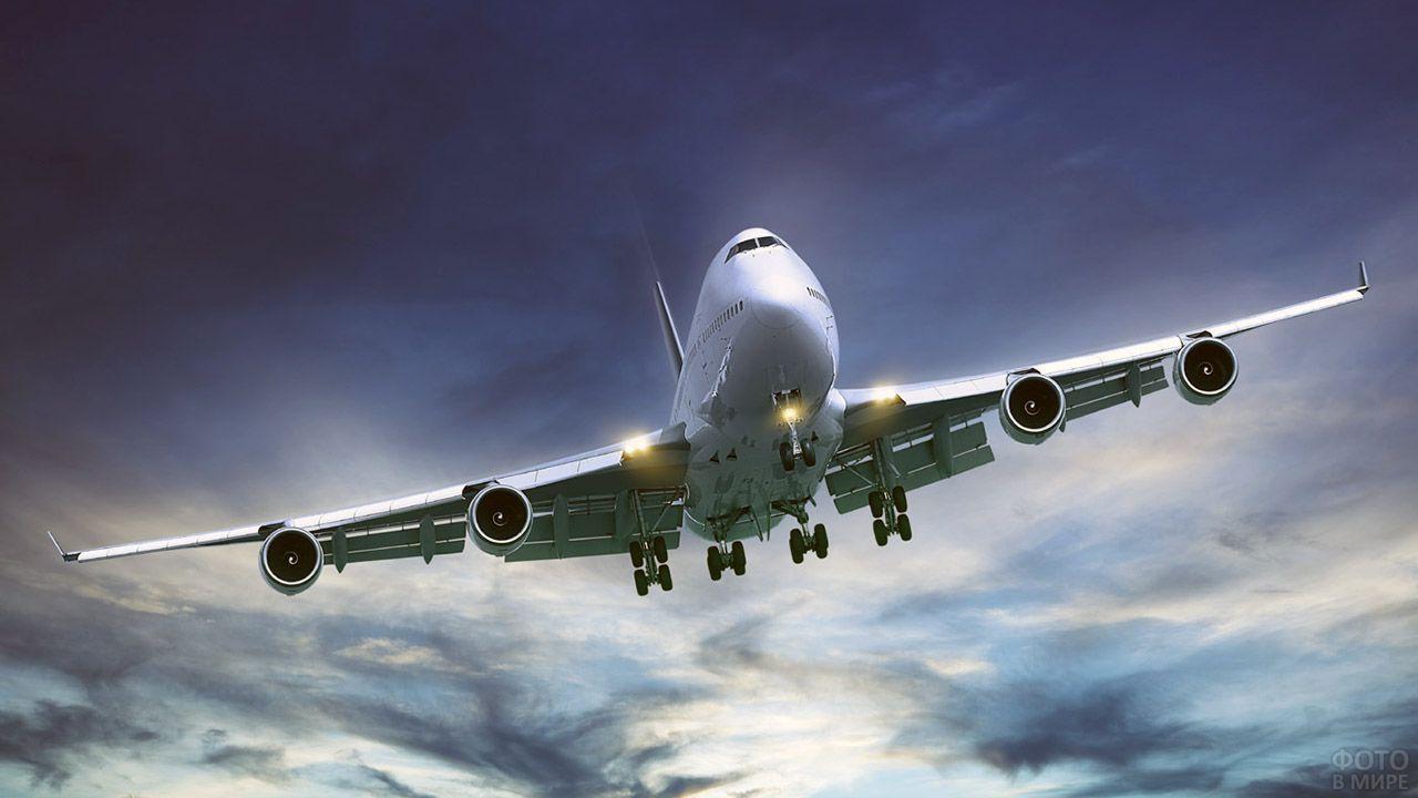 Белый пассажирский самолёт с включёнными огнями в тёмном небе