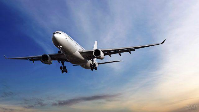 Белый пассажирский самолёт в лучах солнца