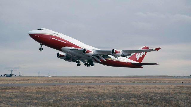 Боинг в бордовой раскраске взлетает над полем