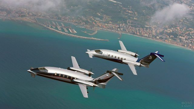 Два бизнес-джета летят над побережьем параллельным курсом