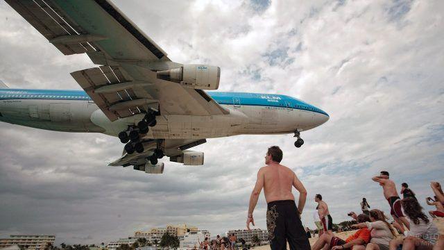 Низколетящий самолёт над головами отдыхающих людей